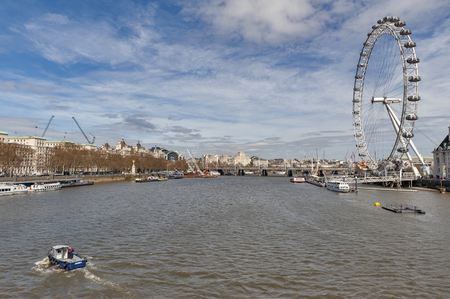 London, UK - April 2018: Cityscape of London from Westminster Bridge over the River Thames with famous London Eye, a giant Ferris wheel, popular tourism landmark of the city of London, England Editorial