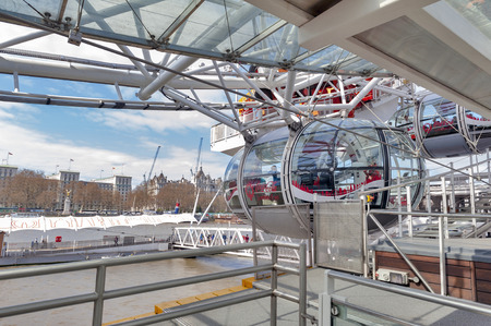 London, UK - April 2018: Ovoidal passenger capsule arriving at boarding platform of the London Eye, a popular giant Ferris wheel, iconic landmark of London, located on the South Bank of River Thames in London, England
