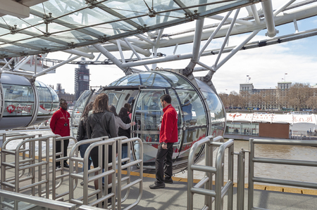 London, UK - April 2018: Passengers queuing to board a capsule of the London Eye, a popular giant Ferris wheel, iconic landmark of London, located on the South Bank of River Thames in London, England