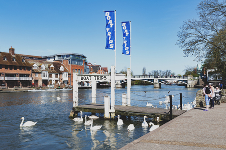 Berkshire, UK - April 2018: A tourist boat cruise pier by the River Thames located between the towns of Windsor and Eton in Berkshire