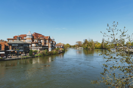 Berkshire, UK - April 2018: The River Thames flowing through Windsor and Eton, twin towns, in Berkshire, in the South East of England, joined by Windsor Bridge Editorial