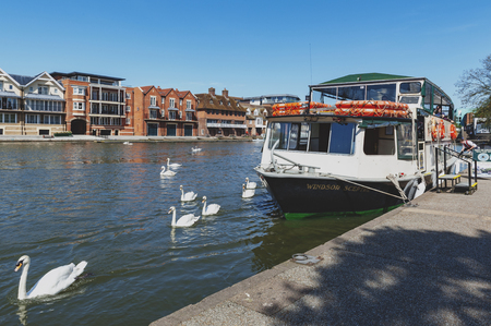 Berkshire, UK - April 2018: Tourist boat cruise at a pier by the River Thames located between the towns of Windsor and Eton in Berkshire