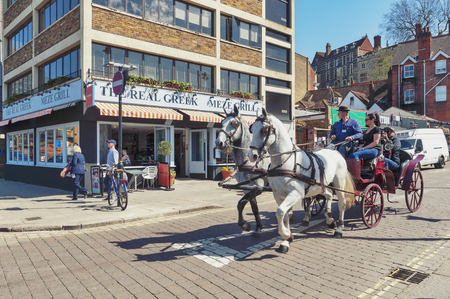 Windsor, UK - April 2018: Tourists enjoying a sightseeing tour by a vintage hackney carriage drawn by white horses in the town of Windsor in Berkshire, England