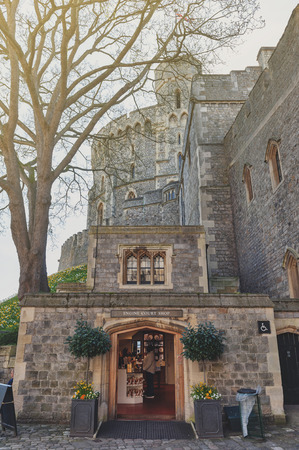 Windsor, UK - April 2018: Souvenir shop behind Edward III Tower inside The Upper Ward or The Quadrangle of Windsor Castle, a royal residence palace and major tourist attraction at Windsor in county of Berkshire, England, UK