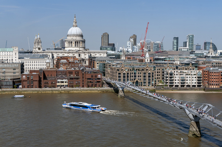 London, UK - April 2018: The London Millennium Bridge, a suspension footbridge for pedestrians crossing the River Thames linking Bankside with the City of London, with skyline of London and St Paul Cathedral seen in background