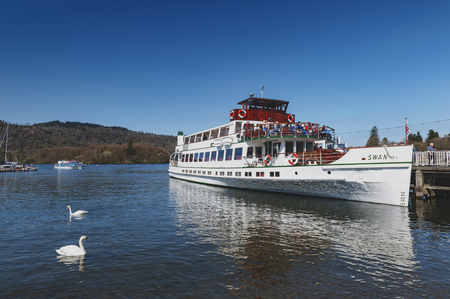 South Lakeland, UK - April 2018: Bowness Pier with boats for hire and tourist cruises at Bowness-on-Windermere, a small tourist resort town on the banks of Windermere in Lake District, England Editorial