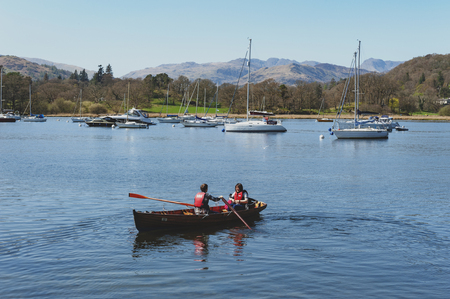 South Lakeland, UK - April 2018: Tourists rowing boat on scenic Lake Windermere in Lake District National Park, North West England, UK