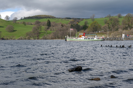 Eden, UK - April 2018: A vintage steam boat named The Western Belle waiting for passengers for the lake cruise at the pier on Ullswater in Lake District National Park, England