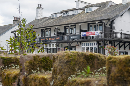 Eden, UK - April 2018: Front facade of two-storeyed building of Pooley Bridge Inn, a local family run accommodation located in the center of Pooley Bridge village near Ullswater, famous English lake in the Lake District of England