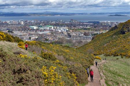 Edinburgh, Scotland - April 2018: Tourist walking through grassy slopes of hills on a hillwalking route up to Arthur's Seat, the highest point in Edinburgh located at Holyrood Park, Scotland, UK