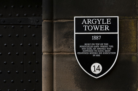 Edinburgh, Scotland - April 2018: Information sign of Argyle Tower on a stone building wall inside Edinburgh Castle, popular tourist attraction and landmark of Edinburgh, capital city of Scotland, UK