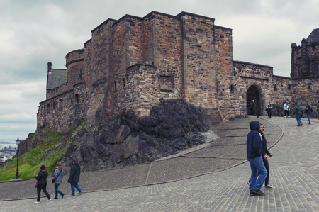 Edinburgh, Scotland - April 2018: Tourists at Foog's Gate, the principle gate to the Upper Ward inside Edinburgh Castle, popular tourist attraction and landmark of Edinburgh, capital city of Scotland, UK Editorial