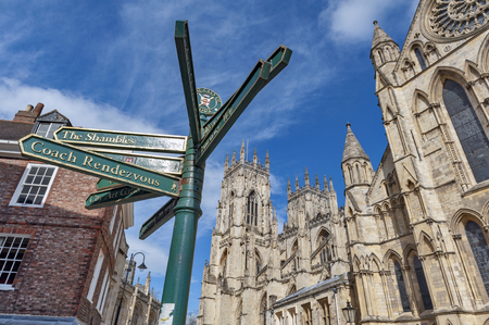 York, England - April 2018: Direction signpost in front of York Minster, the historic cathedral built in English gothic architectural style and major tourist landmark of the City of York in England, UK