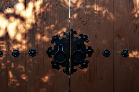 Light and shadow on Korean wooden door panels decorated with old black metallic ring handles at a house in ancient village in Jeonju, South Korea
