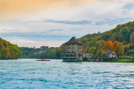 Schaffhausen, Switzerland - October 2019: Sightseeing boat taking tourists to the Rhine Falls, famous and biggest waterfall in Europe on the Rhine River in Switzerland