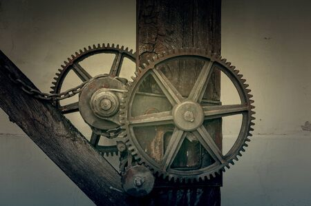 The machine gear of engaging old rusty metal industrial cogwheels installed on wooden structure at a farmhouse