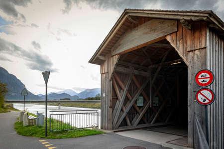 Vaduz, Liechtenstein - October 2019: The Alte Rheinbrücke, an old wooden roofed bridge over the river Rhine on border between municipalities of Vaduz in Liechtenstein and Sevelen in Switzerland