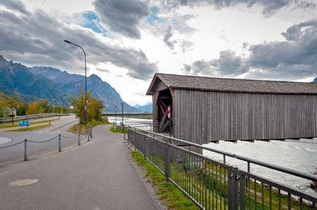 Vaduz, Liechtenstein - October 2019: The Alte Rheinbrücke, an old wooden roofed bridge over the river Rhine on border between municipalities of Vaduz in Liechtenstein and Sevelen in Switzerland Editorial