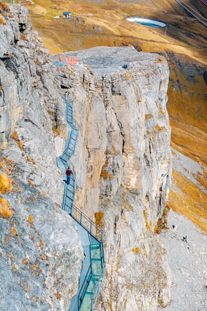 Lauterbrunnen, Switzerland - October 2019: Tourists walking on the Thrill Walk, the cliff pathway down into vertical walls of imposing rock massif located under Birg cableway station at Schilthorn mountain in the Alps, Switzerland