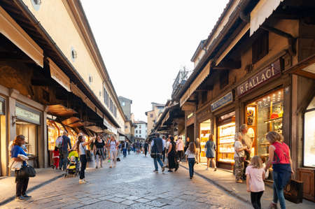 Florence, Italy - October 2019: Tourists walking on the famous Ponte Vecchio (Old Bridge), a medieval stone arch bridge with shops built along it over the Arno River, in Florence, Italy Редакционное
