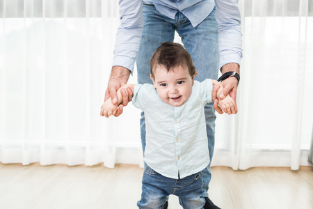 cute guy: family, child, childhood and parenthood concept - happy little baby learning to walk with father help at home Stock Photo