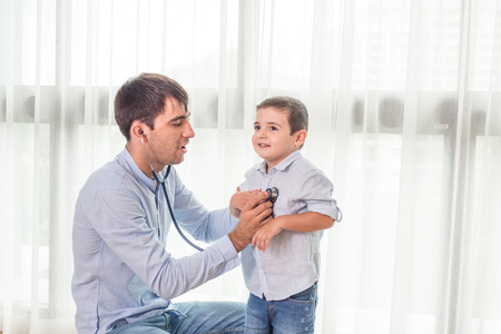 cute guy: Father and Son playing doctors with boy holding a stethoscope and listening to doctors heart as part of therapy. Stock Photo