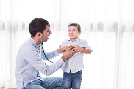 Padre e hijo jugando a los médicos con niño sosteniendo un estetoscopio y escuchando a los médicos corazón como parte de la terapia. Foto de archivo - 87645174