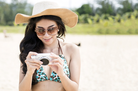 Summer beach woman holding camera taking pictures looking at camera during summer holiday vacation travel at the ocean. Foto de archivo - 95581472