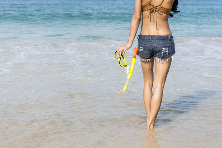 A woman's body is standing with her back to the sea, in a Denim shorts and in her hands a mask for diving, a background of blue sea water. Foto de archivo - 95563921