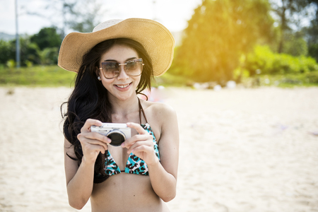Summer beach woman holding camera taking pictures looking at camera during summer holiday vacation travel at the ocean. Foto de archivo - 95581477