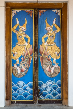 Ancient wooden door with old painting pattern is locked