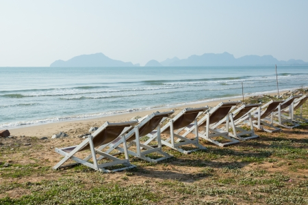 White chairs on the beach, the sea and the mountains.