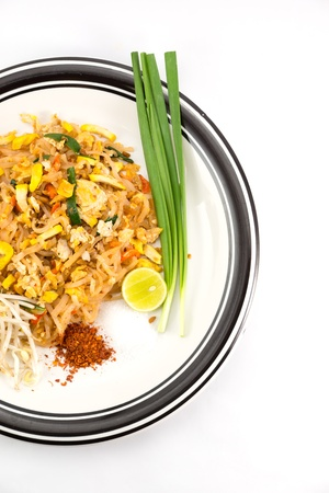 Pad-thai on plate and side dishes on white background