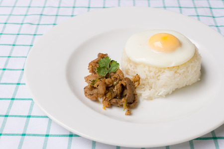 Pork fried with garlic and fried egg on rice