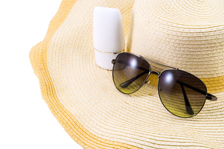 Sunglasses and sunscreen on Hat on isolated white background