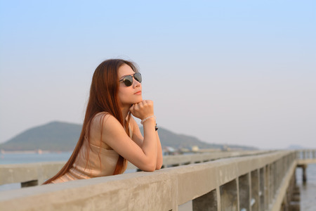 Asian women wear sunglass on the bridge Stock Photo