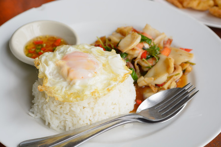 Steamed rice Fried basil leaves with mixed seafood and topped with fried egg
