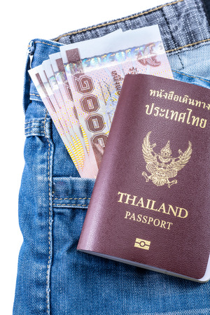 Thai Money 1000 Bath and Thailand passport on blue jeans isolated on white background
