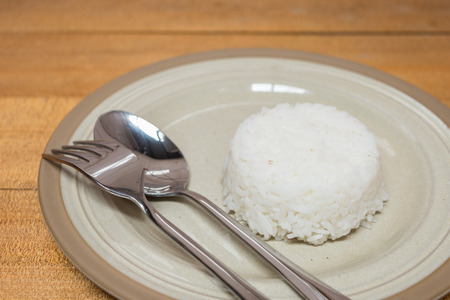 cooked rice: Cooked rice and spoon and fork on plate on wooden table Stock Photo