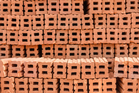 structuring: Stack of red clay bricks wall building
