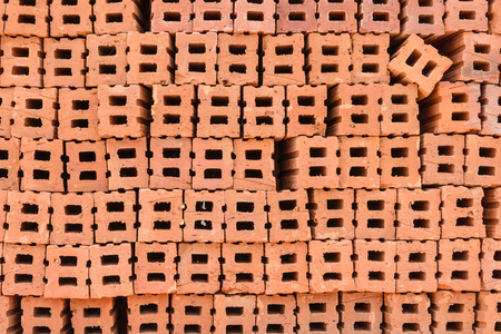 formatting: Stack of red clay bricks wall building