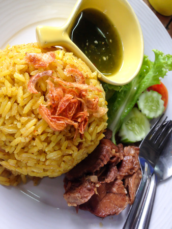 rice  with  curried  chicken with roasted beef on dish and spicy sauce