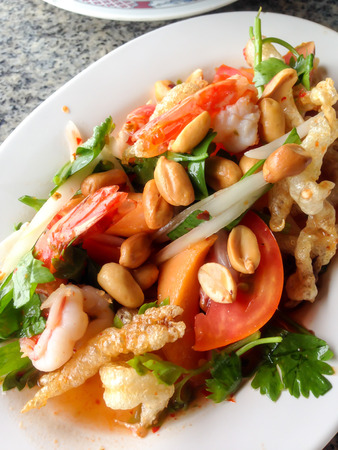 crackling: pork crackling mixed with shrimp, squid and vegetable on a plate Thai local food