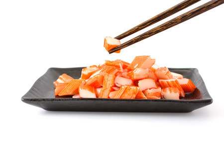 luscious: Imitation Crab Stick with chopsticks in a black plate isolated on white background Stock Photo