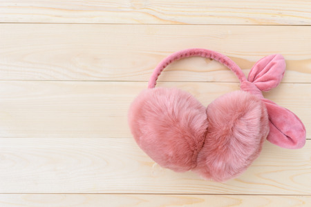 table top: top view pink earmuffs on wooden table