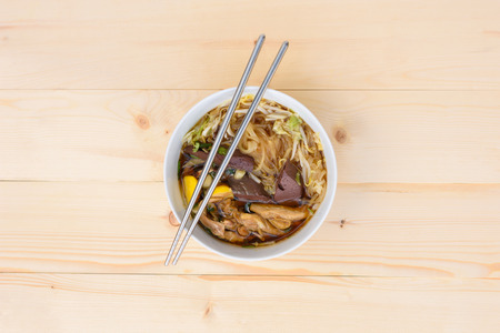 noodle soup: noodle soup with chopsticks in bowl on a wooden table, top view, Thai local food Stock Photo