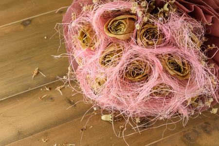 closeup a bouquet of dried flowers on wooden table