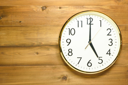 wall clock on the wooden wall at 5am or 5pm