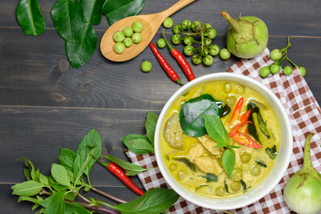 green curry with chicken (Kang Keaw Wan Gai) with brown tablecloth and vegetable on wooden background top view, Thai local food