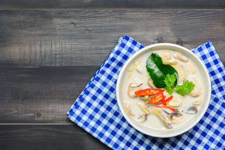 coconut milk soup with chicken or Thai chicken coconut Soup ( Tom Kha Gai ) on wooden table top view, Thai local food